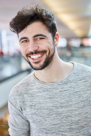 Happy young man with beard and gray shirt in shopping mall