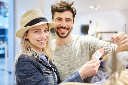 Young happy couple shopping for clothes is looking for special offers
