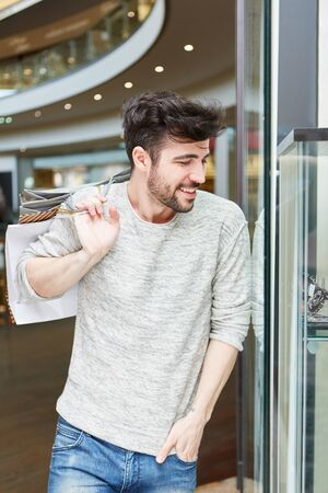 Young man as a customer shopping with bags in the mall Banque d'images