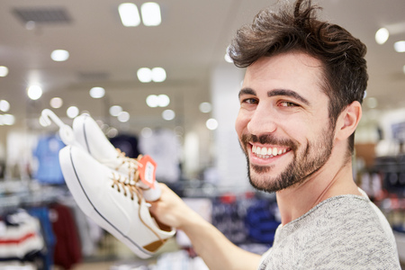 Happy young man is happy about matching shoes in fashion shop Lizenzfreie Bilder