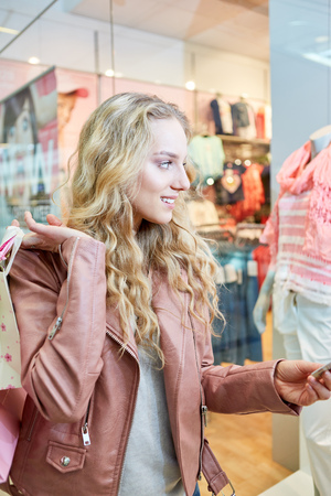 Young blond woman shopping around in front of a fashion store