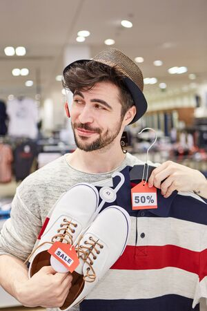 Young man in fashion shop finds special offers while shopping for fashion Lizenzfreie Bilder