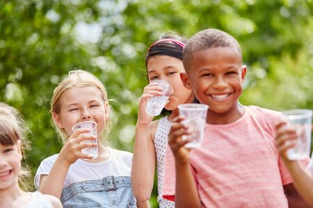 Children with plastic cups drinking water in summer in the park