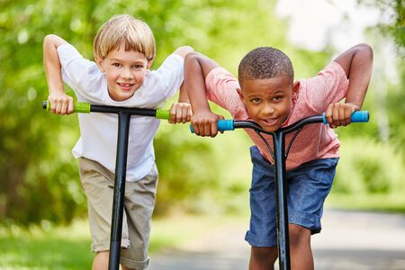 Two boys excited about race with scooters in the park