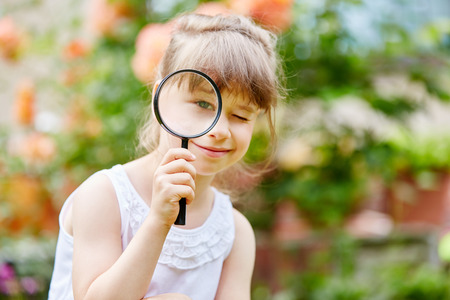 Girl as detective with magnifying glass exploring the world Stock Photo