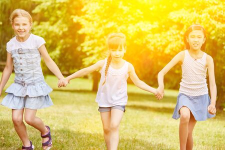 Group of girls walking together in the park in summer