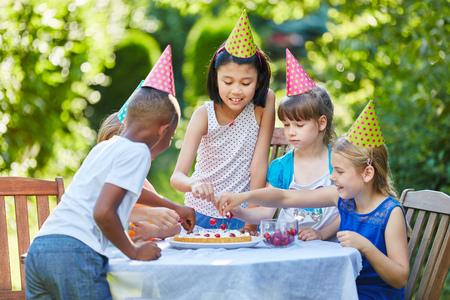 Molti bambini festeggiano insieme con la torta di compleanno alla festa dei bambini Archivio Fotografico - 90327328