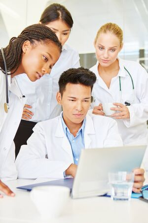 Doctors and nurse working with computer in workshop as team