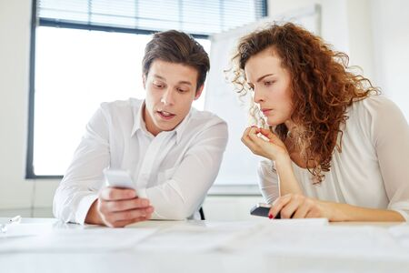 Business people with smartphone reading SMS news Stock Photo
