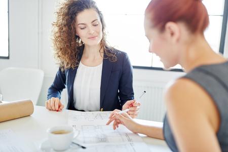 Teamwork during meeting between businesswomen checking draft