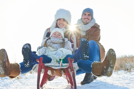 Happy family with sled in winter having fun together