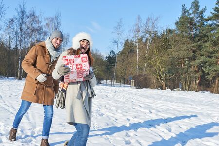 Happy couple in wither with gift walking on the snow