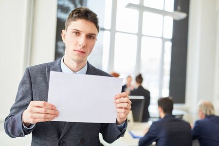 Serious man as candidate holds blank sign in business office Stock Photo