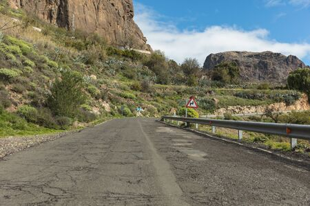 Street with broket sphalt and curve in Gran Canaria road with double curve road sign Banque d'images