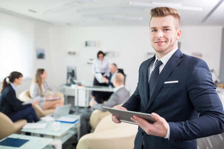 Portrait of smiling young businessman holding tablet computer in meeting room at office