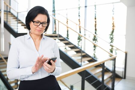 Confident mature businesswoman using smartphone while standing in office Banque d'images