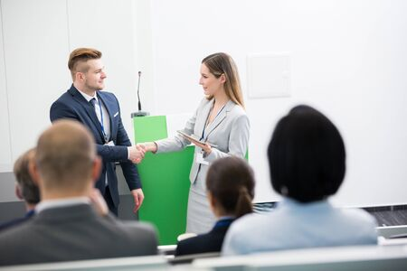 Confident businesswoman shaking hands with colleague in front of audience at lecture hall