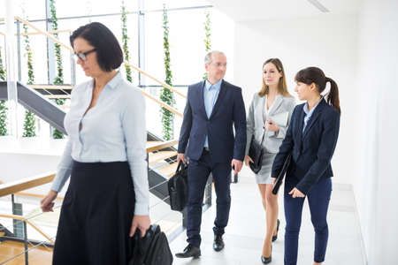 Male and female executives walking on corridor in office