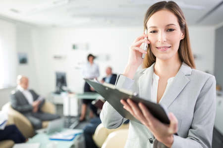Confident businesswoman using mobile phone while holding clipboard in meeting room at office