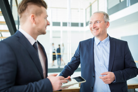 Confident businessman smiling while communicating with colleague in office Banque d'images