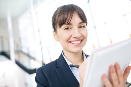 Closeup portrait of businesswoman smiling while writing on document in office Banque d'images