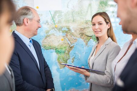 Portrait of confident businesswoman standing with colleagues by world map in lecture hall