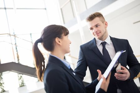 Confident businessman discussing with female colleague over clipboard in office