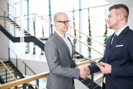 Confident businessman holding digital tablet while shaking hands with male colleague against staircase in office Banque d'images