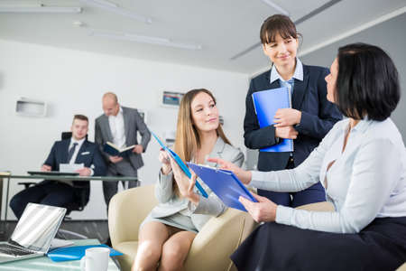 Female executives discussing over clipboards with male colleagues in background at office