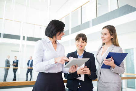 Mature female professional discussing over tablet computer with colleagues in office