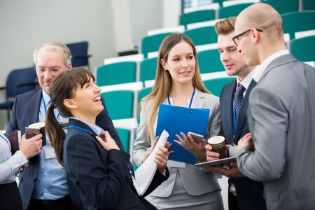 Young businesswoman laughing while colleagues discussing in lecture hall