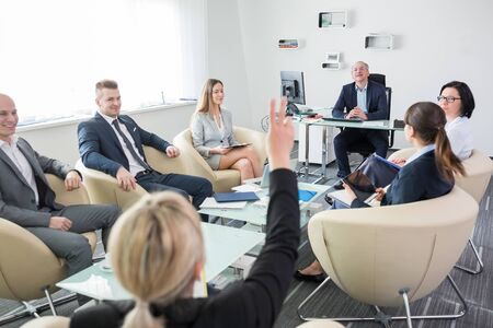 Manager looking at female executive raising hand during meeting in office Banque d'images