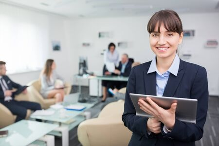 Portrait of smiling young businesswoman holding digital tablet in meeting room at office