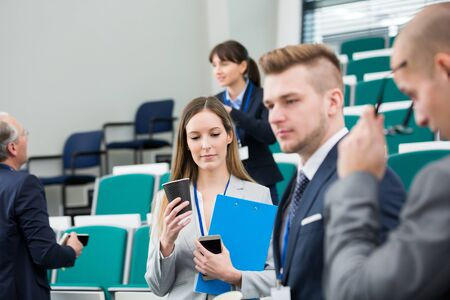 Confident businesswoman holding disposable cup and clipboard while standing with colleagues in lecture hall