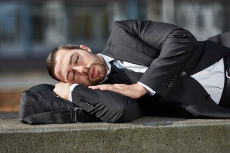Overworked business man is sleeping relaxed outdoors in a break