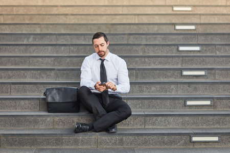 Businessman writes SMS with smartphone app while sitting on stairs