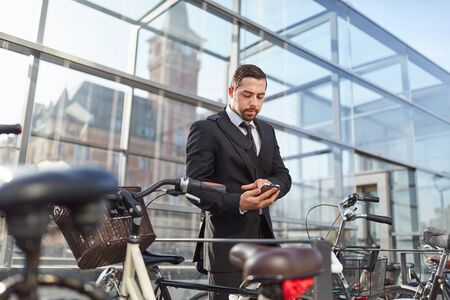 Business man with smartphone app unlocks smart lock on bicycle Banque d'images
