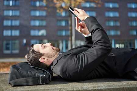 Lying business man writes a text message on his smartphone