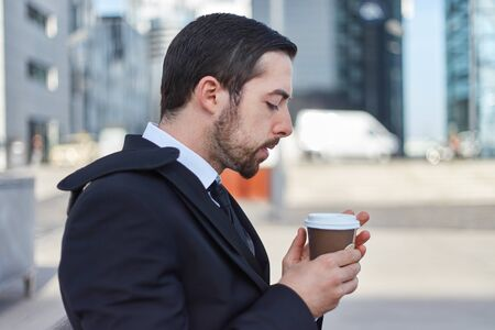 Business man takes a break and drinks a mug of coffee outdoors