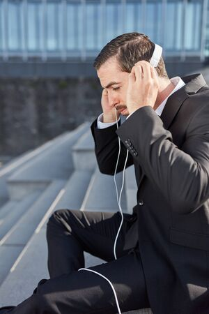 Businessman listens to music or audiobook streaming through headphones