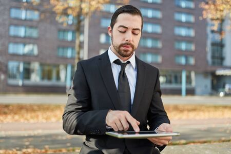 Business man using tablet computer outdoor researching on the internet