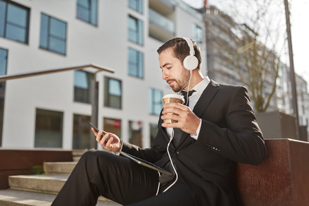 Businessman drinks a coffee and uses a smartphone app