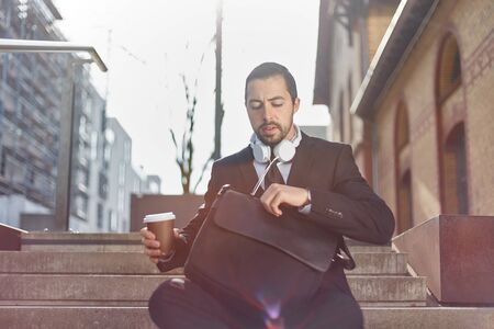 Businessman with coffee mug and briefcase is taking break in the city