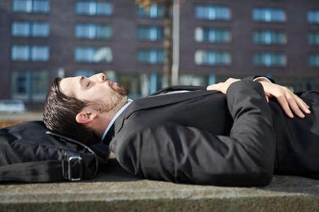 Homme d'affaires est fatigué et fait une sieste à l'extérieur Banque d'images
