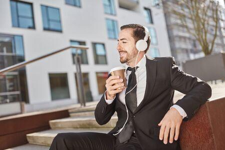 Homme d'affaires souriant boit une tasse de café et écoute de la musique Banque d'images