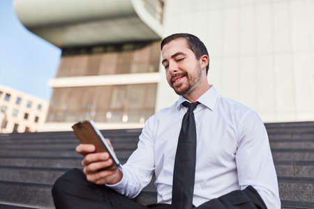 Young businessman reading SMS message on smartphone