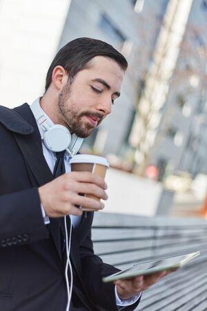 Homme d'affaires regarde une tablette et boit une tasse de café