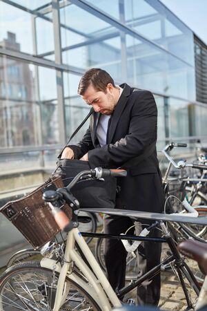 Business man as a commuter looks for the bicycle key