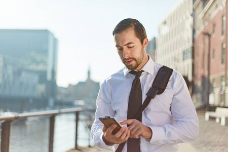 Young businessman typing SMS on smartphone while walking in the city as mobility concept