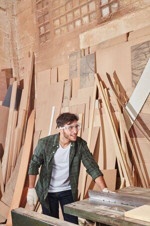 Carpenter with circular saw processing wood